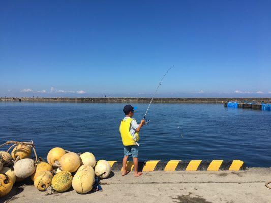 ライフジャケットを着て港で釣りをする男の子