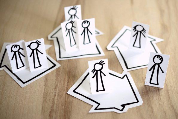 人の絵が描かれた紙が乗った、家の形の紙が4つ。ステイホームを表す